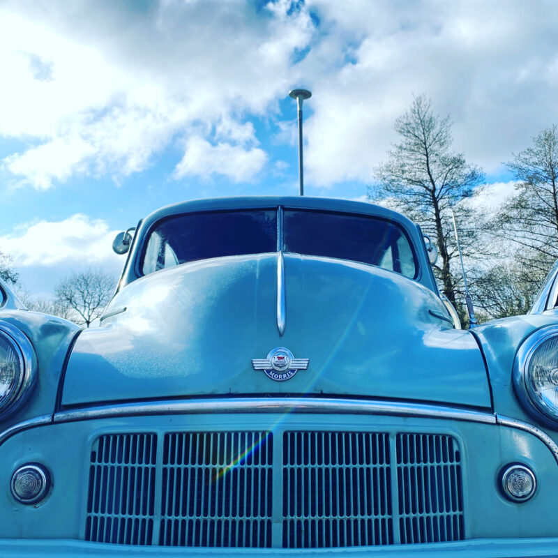 Blue Morris Minor car, under blue sky