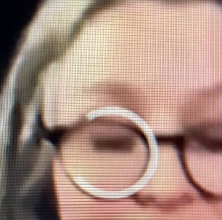 Face of a woman with a circular computer frozen circle over her glasses